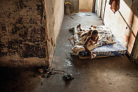 Two boys lie on a mattress in a corridor of the former Grand Hotel building. Once a luxury destination for the wealthy and the continent's biggest hotel, the building is now a concrete shell and home to about 6,000 squatters. Those unable to occupy one of the rooms sleep in the corridors, basements and even on the roof of the building.