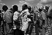 Somali men wait in queue outside a registration and food distribution point in the IFO Camp of the Dadaab refugee camp in northeastern Kenya. Hundreds of thousands of refugees are fleeing lands in Somalia due to severe drought and arriving in what has become the world's largest refugee camp. Photo: Sanjit Das/Panos