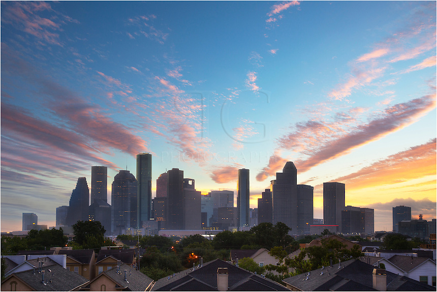 On a glorious morning in the largest city in Texas, the clouds ligut up as the sun prepares to rise over the Houston Skyline. This view of downtown looks nearly directly east. The JP Morgan Tower rises in the cool air as the city begins to awaken from a night's slumber.