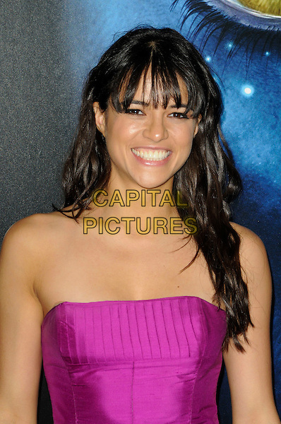 "MICHELLE RODRIGUEZ.The Los Angeles premiere of ""Avatar"" at Grauman's Chinese Theatre in Hollywood, California, USA..December 16th, 2009.headshot portrait strapless pink purple magenta fringe bangs hair half length smiling .CAP/ROT.©Lee Roth/Capital Pictures"