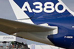 Airbus A380 jet airliner tail (in generic Airbus colours) and hospitality chalet at the Farnborough Air Show, England. The huge tail of the largest airliner in the world, scales the perspective of the corporate building alongside. At the 2014 show, Airbus announced new business worth more than $75m for 496 aircraft, a new record for the company. The Airbus A380 is a double-deck, wide-body, four-engine jet airliner manufactured by Airbus. It is the world's largest passenger airliner, and many airports have upgraded facilities to accommodate its size.