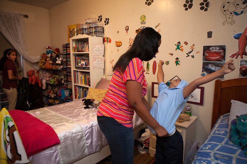 Yokayra Fernandez-Haghighi helps her son, Jesus Haghighi, 7, get ready for school watched by her daughter Victoria, 12, left, in their apartment in Fordham Heights in The Bronx, NY on September 11, 2013.