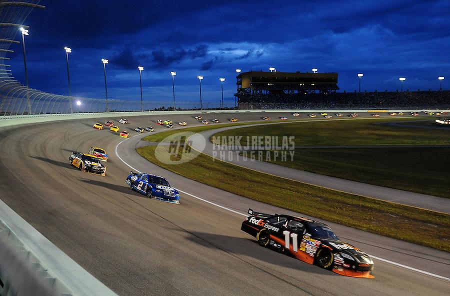 Nov. 22, 2009; Homestead, FL, USA; NASCAR Sprint Cup Series driver Denny Hamlin (11) leads Kurt Busch (2) during the Ford 400 at Homestead Miami Speedway. Mandatory Credit: Mark J. Rebilas-