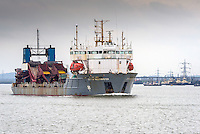 The dredger, City of Westminster steams upriver on the River Thames.