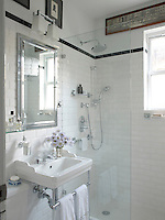 This small bathroom has been rendered as spacious as possible with gleaming white tiles and expanses of glass