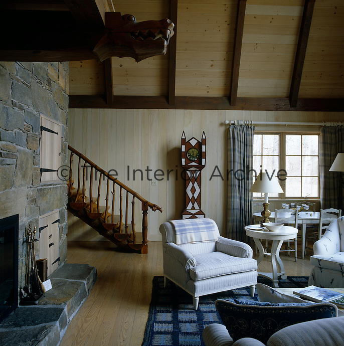 A fireplace with a granite chimneybreast dominates this Swedish-style living room which is furnished in blue and white