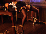 Sexy half-naked asian woman lying on a table in a provocative pose tied up with Japanese rope bondage Shibari