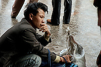 Newly arrived migrant outside Shanghai Railway station, holding onto his baggage.