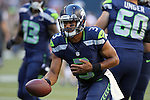 Seattle Seahawks quarterback Russell Wilson hands off against the Denver Broncos at CenturyLink Field in Seattle, Washington on  August 17, 2013. The Seattle Seahawks beat the Broncos 40-10.     ©2013. Jim Bryant Photo. All Rights Reserved.