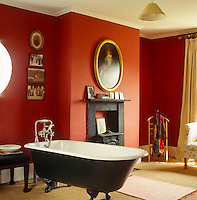 Old family photographs and a gilt-framed portrait hang on the walls of this deep red bathroom