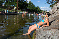 Attractive young woman in a blue bikini sunbathes in the wading area of Barton Springs Pool, Austin, Texas.