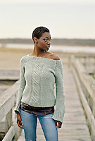 African American Woman Looking Off While Standing On A Boardwalk in Southampton, NY