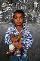 Farman, 3, poses for a portrait with a soft toy in the Guria Non-Formal Education center in the middle of the Shivdaspur red light district, Varanasi, Uttar Pradesh, India on 20 November 2013. Guria uses the soft toys as a form of therapy for the children of the women in prostitution and also use it as signals of the children's emotional wellbeing.
