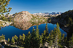 Reflections of the beartooth mountain range in a small mountain lake in the beartooth wilderness in montana