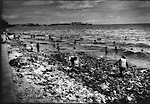 Squatters, mostly children, picking through rubbish washed up along beach on Manila Bay, Philippines.