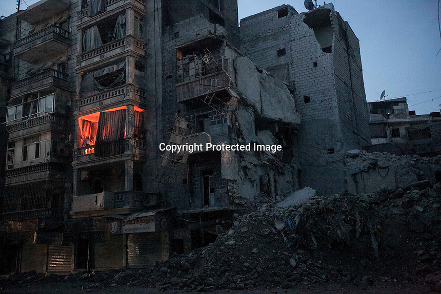 In this Thursday, Nov. 29, 2012 photo, night falls on a Syrian-rebel controlled area in Sa'ar street as a house apartment is iluminated by fire used by one family to keep them warm beside a destroyed buildings, among those the Dar Al-Shifa hospital, which was targeted by one warplane last week killing dozens, among medical staff and civilians, in Aleppo, the Syrian's largest city. (AP Photo/Narciso Contreras).