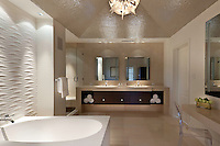 The guest bath has a glass mosaic ceiling and architectural relief wall panel detail at the tub