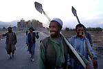 Afghan road construction workers return home in the evening Oct 21, 2002 near the ruins of the former Defense Ministry building in Kabul, Afghanistan. Much of the neighborhoods of West Kabul lie in ruins after nearly 20 years of war and are just now beginning to be rebuilt.