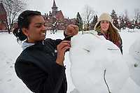 Students make a snowman on the UVM Campus Green in front of Old Mill. Winter UVM Campus