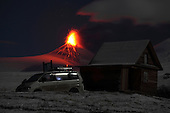Nighttime Eruption of Kliuchevskoi (Klyuchevskoy) Volcano, Kamchatka, Russia with a mountain hut and car in the foreground. Persistent strombolian activity throws lava into the air and onto the flanks of the symmetrical cone of the massive stratovolcano.