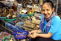 Herbalist at the Vientiane Morning Market,  a large collection of indoor and outdoor stalls selling pretty much anything. There are two floors - the first floor sells mostly textiles, electronics, and watches; the second floor has clothing, gold, and jewelery. Expect to pay about one third or one quarter of the first price you are offered. Despite the name it is still struggling into operation at 8:00 and remains open until around 16:00.