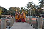 a group of Tibetan monks, in their ceremonial garb, walk down a pier in the Florida Keys to toss sand from their mandala back into the sea