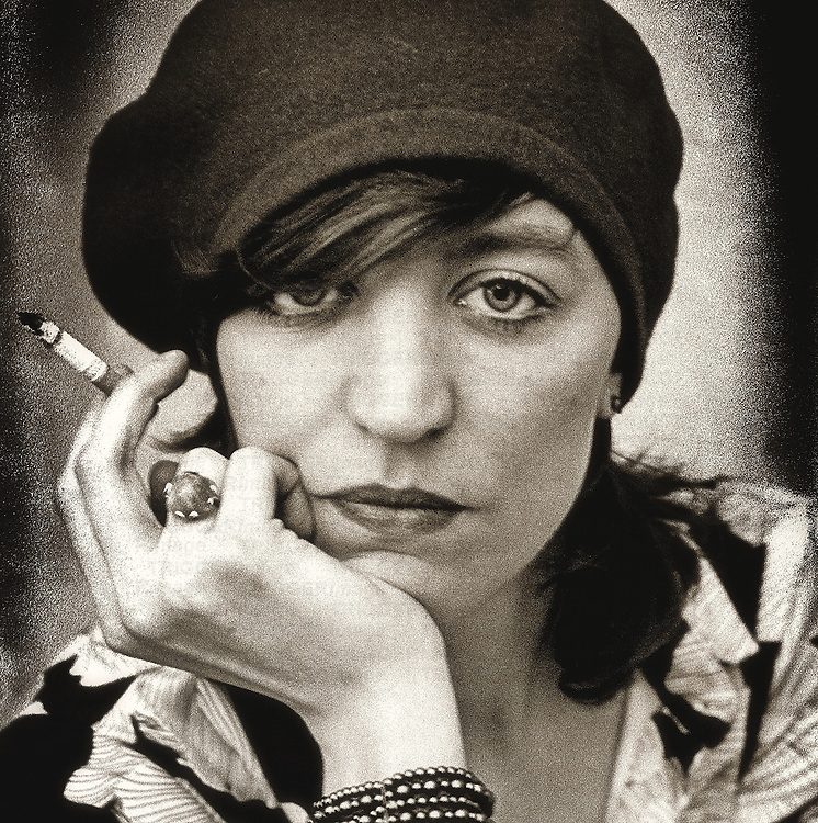 Close up of a middleaged woman wearing a hat and smoking a cigarette looking sternly at the camera