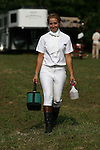 A groom makes her way to prepares horses before four in hand coaching event in Locust, New Jersey.