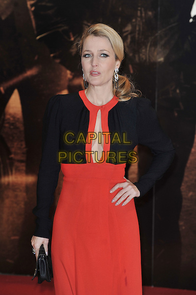 """Gillian Anderson.The """"Mission : Impossible Ghost Protocol"""" UK premiere, BFI Imax cinema, Waterloo, London, England..December 13th, 2011.Mi4 MI:4 half 3/4 length black clutch bag jacket dress red plunging neckline cleavage .CAP/MAR.© Martin Harris/Capital Pictures."""