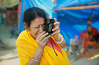 A Bengali woman taking a picture of Naga Sadhus during the Kumbh Mela in Haridwar, India. Pilgrims flock from all corners of India to take a holy dip in the river Ganges during the fair and the number multiplies many times during the Royal Bath dates.