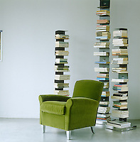 In this living room tall steel book towers are an elegant and space-saving option to the standard bookcase