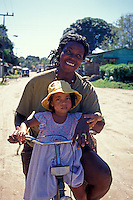 Mother and daughter riding a bicycle in the village of Cahuita on the Caribbean coast of Costa Rica