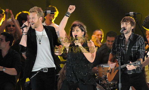 Lady Antebellum.The 45th Annual CMA Awards, Country Music's Biggest Night, held at Bridgestone Arena, Nashville, Tennessee, USA..November 9th, 2011.stage concert live gig performance music in on half length black suit jacket white top side dress singing guitar arm in air.CAP/ADM/LF.©Laura Farr/AdMedia/Capital Pictures.