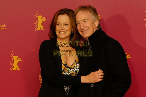 """SIGOURNEY WEAVER & ALAN RICKMAN.Photocall for """"Snow Cake"""" at the 56th Berlin (Berlinale) Film Festival, Berlin, Germany..February 9th, 2006.Ref: KRA.half length black coat cardigan smiling.www.capitalpictures.com.sales@capitalpictures.com.©Capital Pictures"""