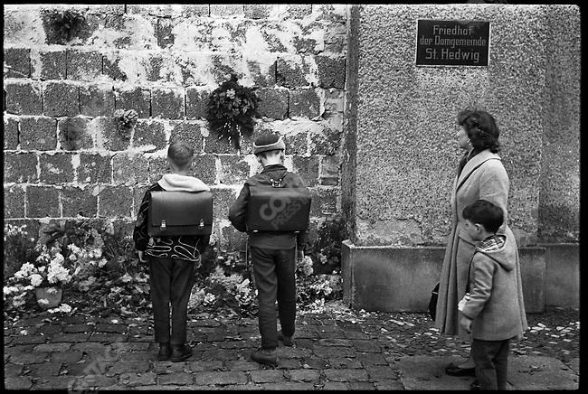 West Berliners at a memorial for a person killed trying to go over the Berlin Wall during it's construction near the border of the French sector, West Berlin, Germany, November 1961