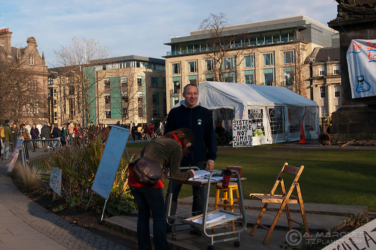 "A passer-by signs a petition at the Occupy Edinburgh camp, St Andrew's Square, Edinburgh. The main tent of the camp can be seen on background, and a sign reading ""System Change Not Climate Change""."