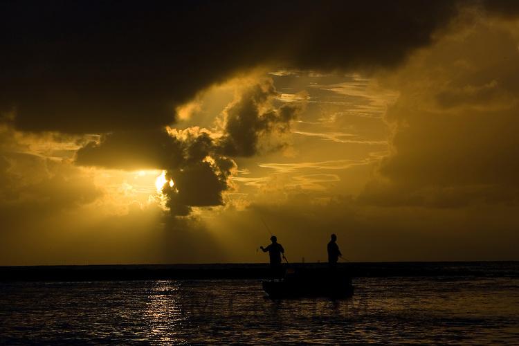 Men fishing at dawn in the Mossman River, Daintree, Australia