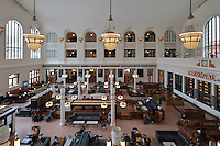 Great Hall of the terminal building of Denver Union Station, in Beaux-Arts style with tall, multi-storey arched windows and bays, 3 huge chandeliers and terrazzo floors, used as a waiting room for trains, Denver, Colorado, USA. The station was originally built in 1881 and rebuilt in 1914, then renovated 2010-14. The original ticket offices on the right are now the Terminal Bar. Picture by Manuel Cohen