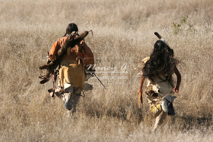 Two Native American Indian men running uphill in the dry grasses of South Dakota