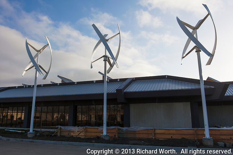 Three vertical axis wind turbines designed for urban applications and able to use wind from all directions, stand in front of the under-construction Zero Net Energy Center near San Francisco, California.