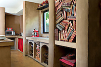 The kitchen has been designed in a Moroccan style from its colour scheme down to the arched alcoves used for storage and the bright red curtain in the place of a cupboard door