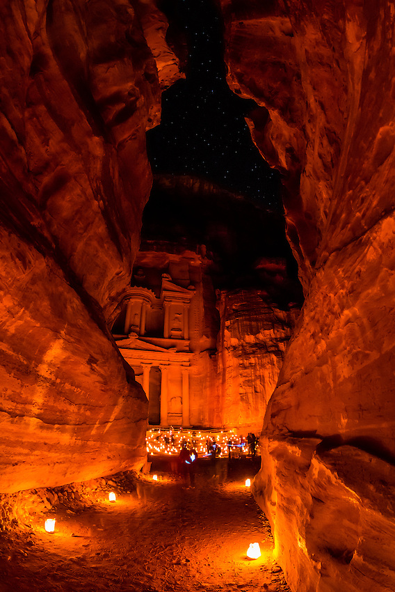 """Approaching the Treasury (Al-Khazneh) from the Siq (a 1200 meter long gorge) in the Petra archaeological site (a UNESCO world heritage site), Jordan. The length of the Siq and the area around the Treasury is candlelit for """"Petra by Night""""."""