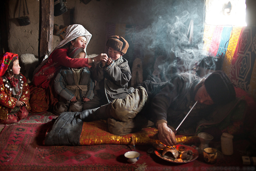 Aziz and his family. Aziz is one of the son of the late Khan, during one of his 3 daily opium smoking session, in his home. He is completely addicted, having smoked regularly since the last 8 years..Kyzyl Qorum, campment of the former deceased Khan, Abdul Rashid Khan..Trekking with yak caravan through the Little Pamir where the Afghan Kyrgyz community live all year, on the borders of China, Tajikistan and Pakistan.