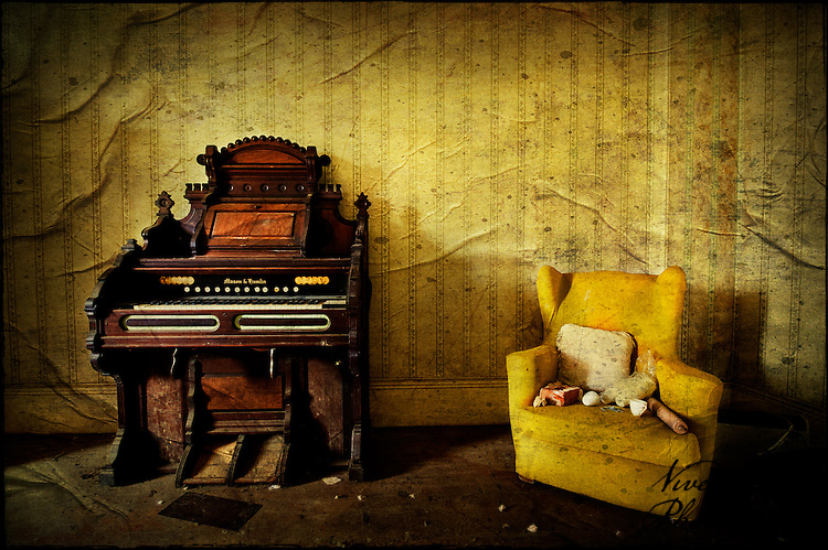 Organ and armchair in abandoned manor house