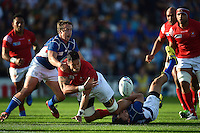 Joe Tuineau of Tonga offloads the ball after being tackled to ground. Rugby World Cup Pool C match between Tonga and Namibia on September 29, 2015 at Sandy Park in Exeter, England. Photo by: Patrick Khachfe / Onside Images