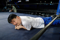 A wrestler takes a break after the warm-up.
