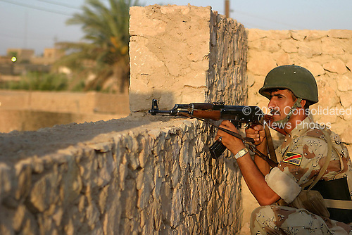 An Iraqi army soldier attached to India Company, 3rd Battalion, 3rd Marine Regiment pulls security from the roof top of a house during a house search in Haditha, Iraq, Aug 5, 2006. (U.S. Marine Corps photo by Cpl. Brian M. Henner) (Released)