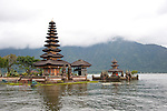 "The Hindu temple of Ulun Danu at Candikuning is one of the iconic images of Bali, Indonesia.  Located in the high hills of the Bedugul, about 30 miles north of Bali's capital city of Denpasar, the temple is built on the shores of the crater Lake Bratan (formed from the sunken crater of a long-dormant volcano).  Much of the inner precincts of the temple is closed to the (non-Hindu) public, but the gardens are spectacular and feature fabulous shrines, statuary, and views.  The iconic tourist image is the two ""water shrines,"" which these days are usually partially submerged in the waters of Lake Bratan."