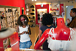 "ADDIS ABABA, ETHIOPIA - NOVEMBER 13: A young women tries a pair of red Prada sunglasses at the ""Lady Shop"" an up-market clothing shop for women on November 13, 2010 in a shopping mall in Addis Ababa, Ethiopia. Some people can afford to buy expensive locally  and imported cloths despite that this one of Africa's poorest countries. (Photo by Per-Anders Pettersson)"
