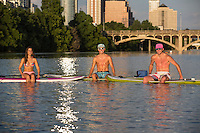 Group of SUP surfers in swimsuits sit on stand up paddle boards and huddle in the middle of Lady Bird Lake amid the majestic Austin Skyline in the background.